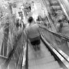 """2011-07-24 This is my wife, riding an escalator in a store. You might notice there is some weirdness going on. That's because it's actually 10 photos stitched together using AutoStitch. I waited about 6 steps after my wife and just started taking a bunch of photos at different angles. The app is looking for common elements to make a panorama, but in this case it was just a blob of photos with the only commonality being my wife and the escalator itself. Fun stuff. Speaking of AutoStitch, I have a blog post that's 80% done about my experience with various iPhone panorama apps. Stay tuned for that!  <a href=""""http://www.jawsnap.net/Daily/year3/11272102_ACXDJ#946317093_ye6Pb"""">[last year]</a> <em>hey, it's Rusty...</em>"""