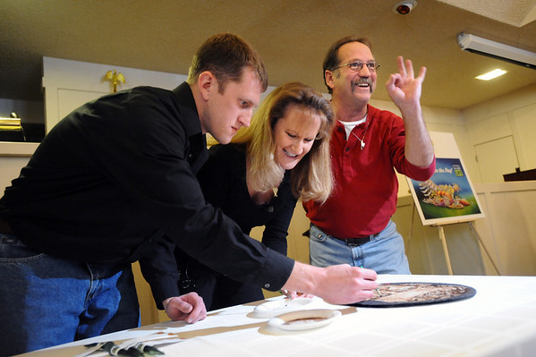 "ORGAN<br /> Anthony Lamirato, right, flashes an a-ok sign to friends and family while adding the finishing touches to a floragraph of his son, Jared, who died almost a year ago and was an organ donor. With Lamirato is his wife, Mary, and son Joshua, who were part of a ceremony at Crist Mortuary to prepare Jared's floragraph for the Donate Life Rose Parade on January 1. <br /> For more photos, see  <a href=""http://www.dailycamera.com"">http://www.dailycamera.com</a>.<br /> Photo by Marty Caivano/Camera/Dec. 14, 2010"