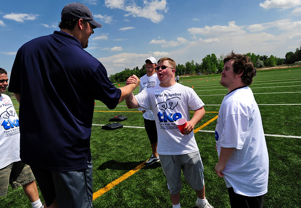 "FOOTBALL<br /> Tyler Polumbus, left, a defensive lineman with the Seattle Seahawks, gets a high-five from Grayson Colegrove, while Alex Schwartz, right, waits his turn. In the background is Ryan Echer, a free agent who frequently trains with Polumbus. The players were teaching a camp for people with developmental disabilities on Thursday. The camp was a partnership between the Boulder Parks and Recreation's EXPAND program and ""Tyler's Kids Outreach"" foundation. <br /> Photo by Marty Caivano/July 7, 2011"