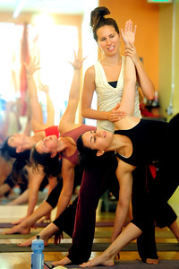YOGA Instructor Kate Sciolino helps Raquel Mayorga with a pose during a yoga class at Om Time in Boulder. Photo by Marty Caivano/July 8, 2011