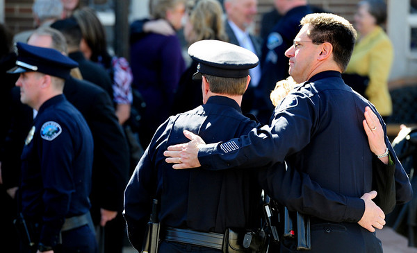 Police officers hug outside the memorial service for long-time Boulder Police Officer Mike Pease. The service was held Friday morning at the Sacred Heart of Jesus Church in Boulder. <br /> Photo by Marty Caivano/Feb. 18, 2011