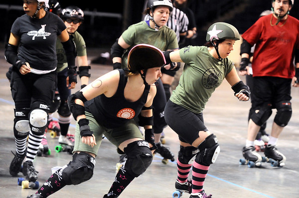 "ROLLER05<br /> Julie ""Angela Death"" Adams, right, jammer for the Green Barrettes, gets through the pack after evading Amy ""Moira Lee DeVoid"" Little, left, during a roller derby scrimmage at the 1st Bank Center in Broomfield.  <br /> Photo by Marty Caivano/Camera/March 15, 2010"