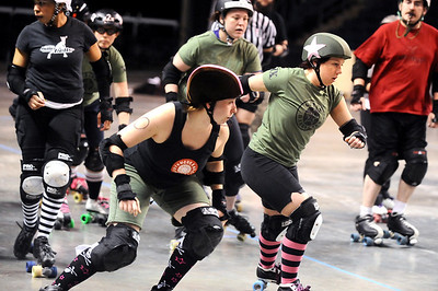 "ROLLER05 Julie ""Angela Death"" Adams, right, jammer for the Green Barrettes, gets through the pack after evading Amy ""Moira Lee DeVoid"" Little, left, during a roller derby scrimmage at the 1st Bank Center in Broomfield.   Photo by Marty Caivano/Camera/March 15, 2010"