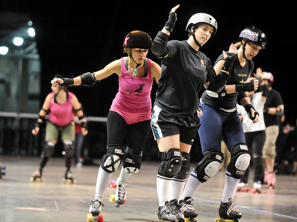 ROLLER07<br /> Heather Juska, left, jammer for the Shotgun Betties, tries to get around opposing blockers during a roller derby scrimmage at the 1st Bank Center in Broomfield.  <br /> Photo by Marty Caivano/Camera/March 15, 2010