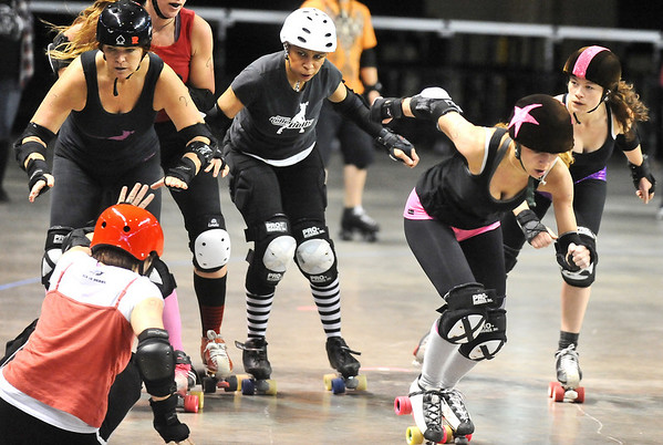 "ROLLER03<br /> Heather Juska, right, jammer for the Shotgun Betties, pushes through the pack after taking down Teresa ""Wicked Sister"" Rusk, left, during a roller derby scrimmage at the 1st Bank Center in Broomfield.  <br /> <br /> Photo by Marty Caivano/Camera/March 15, 2010"