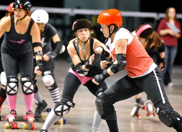 "ROLLER02<br /> Heather Juska, left, jammer for the Shotgun Betties, tries to evade a block from Teresa ""Wicked Sister"" Rusk, right, during a roller derby scrimmage at the 1st Bank Center in Broomfield.  <br /> Photo by Marty Caivano/Camera/March 15, 2010"