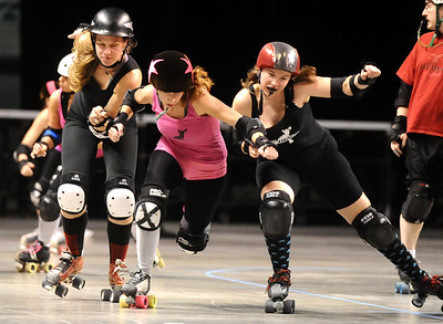 "ROLLER08 Heather ""Juska"" Juska, center, jammer for the Shotgun Betties, pushes through blockers Gabrielle ""Fonda Payne"" Begeman, left, and Jennifer ""Murderface Molly"" Gifford of the Bad Apples during a roller derby scrimmage at the 1st Bank Center in Broomfield.   Photo by Marty Caivano/Camera/March 15, 2010"