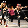 "ROLLER08<br /> Heather ""Juska"" Juska, center, jammer for the Shotgun Betties, pushes through blockers Gabrielle ""Fonda Payne"" Begeman, left, and Jennifer ""Murderface Molly"" Gifford of the Bad Apples during a roller derby scrimmage at the 1st Bank Center in Broomfield.  <br /> Photo by Marty Caivano/Camera/March 15, 2010"