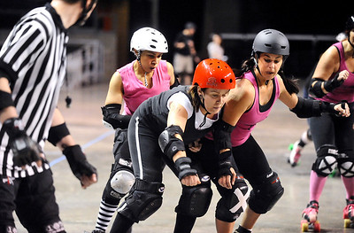 "ROLLER09 Teresa ""Wicked Sister"" Rusk, center, of the Bad Apples, gets some contact from Monica ""Lynn Sane"" Carson, left, and Bobbi ""Bruise-Shea"" Mastalka, right, of the Shotgun Betties, during a roller derby scrimmage at the 1st Bank Center in Broomfield.   Photo by Marty Caivano/Camera/March 15, 2010"