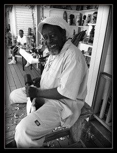 December 6, 2014  This is Vincent, he is a wood carver at the straw market in Nassau.  He has been carving and selling for 30 years.  We visit and buy from him every time we come to Nassau.  He is a true craftsman.  Notice the empty beer bottles on the ground behind him ;)