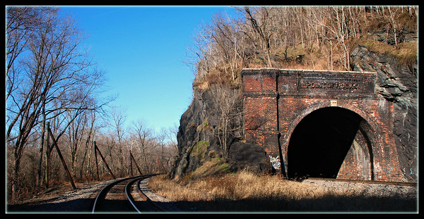 December 30, 2014  Point of Rocks Train Tunnel, Maryand  First constructed in the 1860s, the tunnel was enlarged in 1902 to accomodate larger trains. In the early 1960s, the eastbound track was moved to the outside of the tunnel to accomodate still larger trains. This was done by blasting the rocks on the old alignment outside the tunnel, enlarging the road bed, and dumping the excavation rocks into the canal bed, where they remain today.  http://www.canaltrust.org/discoveries/points.php?pointID=31