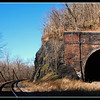 "December 30, 2014<br /> <br /> Point of Rocks Train Tunnel, Maryand<br /> <br /> First constructed in the 1860s, the tunnel was enlarged in 1902 to accomodate larger trains. In the early 1960s, the eastbound track was moved to the outside of the tunnel to accomodate still larger trains. This was done by blasting the rocks on the old alignment outside the tunnel, enlarging the road bed, and dumping the excavation rocks into the canal bed, where they remain today.<br /> <br /> <a href=""http://www.canaltrust.org/discoveries/points.php?pointID=31"">http://www.canaltrust.org/discoveries/points.php?pointID=31</a>"