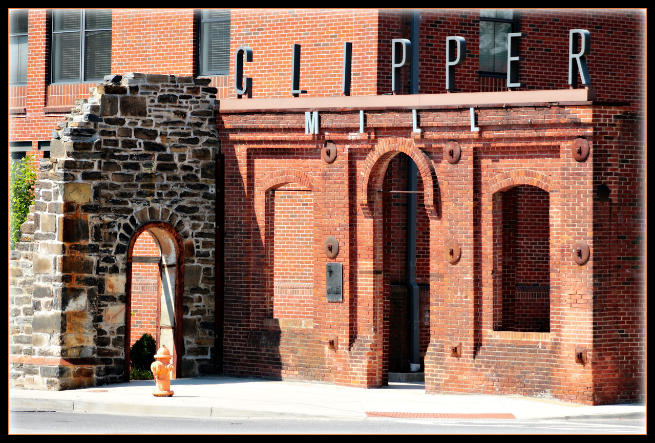 June 17, 2017<br /> <br /> Across the street from the mural in yesterday's POTD is Clipper Mill.   In 1995 there was a horrible fire killing one fire fighter and injuring many more.  This stone wall was left as a memorial to him.  Clipper Mill was reinvented and is now the home to both residential and commercial spaces.  <br /> <br /> The buildings that comprise the Clipper Mill complex date back to the 1850s. As the Poole and Hunt Foundry, the complex was an integral part of Baltimore's and the nation's manufacturing economy as they produced steam engines, steam boilers, the Leffel American double turbine water-wheel, circular and gang saw-mills, crushers for various milling and mining operations, railroad cars and engines, and screw pile lighthouses.  Specifically, the site had close ties to the city and country's burgeoning railroads, which started in Baltimore, as it made major machine pieces for the railroads. <br /> <br /> Here is one of the articles on the fire:<br /> <br /> A Baltimore firefighter was killed and three others were seriously injured Saturday night as they battled a blaze that destroyed a historic warehouse in the city's Woodberry neighborhood.<br /> <br /> Eric Schaefer, 25, died after a stone wall of the 100-year-old building collapsed on him and several other firefighters. It was the fire department's third fatality in 10 years and the first one since 1991.<br /> <br /> Fire officials said they are investigating the cause of the blaze in the Clipper Mill Industrial Park, which drew hundreds of firefighters from units across the city and Baltimore County. Officials speculated that the fire may have been sparked by electrical wires.<br /> <br /> Flames spread quickly through the high-ceilinged, one-story building, possibly fed by flammable chemicals in the space that houses several small businesses, including artists' studios and a furniture-repair store.<br /> <br /> The Associated Press reported that a witness heard five small explosions as the fire raged. Firefighters had brought the blaze under control by 1 a.m. yesterday. Officials said several firefighters were injured when they tried to enter the building. They cut through a garage door, and as soon as they got in, the roof collapsed, causing the granite stone wall to cave in.<br /> <br /> Schaefer, of Baltimore, had been with the fire department about two years. He had recently been married, fire department officials said. The three other badly injured firefighters were in serious but stable condition at local hospitals yesterday.<br /> Samuel Johnston, vice president of the Woodberry Community Association, said the complex dated to 1850 and was used during World Wars I and II to store surplus military equipment.