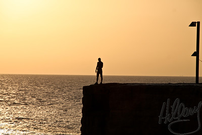 Post 763 11.10.10  Young cliff diver at the edge of the Meditteranean Sea at the ancient port of AKKO ( aka Acre) in Israel. We were there for part of our fall vacation in NOvember ( I am reallly, really slow editing all these photos). There were 2 young boys diving off these cliffs. I saw one dive, then waited as long as I could to catch another, but they just stood instead of diving again. Loved the silhouettes in the late afternoon sun. ** What do YOU think? Should I crop out the light or does it give balance to the image? I'm not sure...