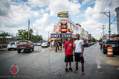 """Post 1029 7.25.12  Welcome to South Philly and the streets  where local cheesesteak places come to bump heads in competition..These young me are looking toward's Pat's Steaks which i behind where I was standing as I took the pic of Geno's.  There is always a line a block long at each of these places so the war appears all tied to my eyes!  This is a photo that I am entering in our local PhillySMUG's photo competition called, """"ShootPhilly""""...ha ha..since I am one of the leaders I made up the competition, but I am NOT one of the judges, fortunately. There are some amazing photographers in this group and it will be hard to pick 26. The 26 images chose will be shown in the gallery of our local Calumet  Photographic store in Philadelphia where we hold our meetings. Have you joined a SMUG near you? It is so much fun and a great opportunity for meeting and networking with other photographers in your area.  If you are interested in seeing our 'contest' gallery you can see it HERE   I have to tell you I was shocked to see the welcome and respond to my picture yesterday.Wow, thank you. I have been so hit or miss with posting on the Dailies, but so appreciate your time to notice and comment on my shot from the Florida Gulf Coast yesterday. That was a terrific boost to me! I have been so busy with work, the PhillySMUG and just stuff, I have hardly done much photography and it is with the Dailies..whether I post old or new photos that I really help myself to grow as a photographer. I really love this community and am totally inspired by your work. Thank you for always welcoming me back when I have time to post...It's like coming home.. :)"""