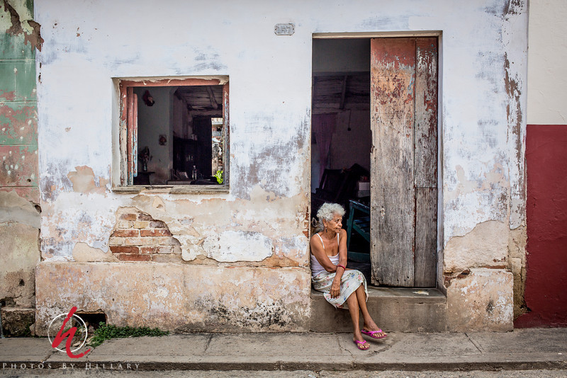 """<font size=""""4""""><b><font color=""""Yellow"""">Daily Post 1097- 62/365  3/03/2014 - Lady in the Doorway / Trinidad, Cuba  LIfe is quiet and very small in Cuba. So many people sit in their doorways or at their open windows.. Often alone, but often chatting with others. Their inside lighting at night is very low..maybe a television flickering away with the family group in a smalll room watching. With the heat of summer (and maybe all year 'round) their doors and windows appear to be more open than not.  This scene was quite typical.   Thank you so much for your kind comments an indulgence as I continue to slowly sort through my Cuba images. It is good for me to isolate images finally to help me decide which ones I will enter into competition. Your thoughts really help me see them in different ways, too. Thank you all… I am glad also to finally upload a bunch to SmugMug for safe keeping as I have also keep the files on all my memory cards intact until I decide what I'm keeping and what I'm getting rid of just as back up..that's a lot of memory cards sitting around in a baggie! :)  Thanks, too, for your wonderful reception to my """"D"""" yesterday. I was so impressed with all the """"G""""s you posted..I couldn't begin to see one, then all of a sudden I did see a """"G"""" yesterday so now I'm looking forward to posting next Sunday to show off mine..  Have a good week everyone!"""