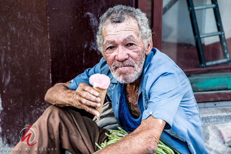 """<font size=""""4""""><font color=""""Yellow"""">Post 1047   12/365 1/12/2014 - A moment to share ice cream in the heat of the day with this fellow…  This fellow was selling green beans in the shade on the sidewalk in a small town called Guanacoboa in Cuba.... His face was  full of the character only seen in someone who has had  long hard life  and was one that I was interested in photographing..I knew Steve was buying some ice cream cones and asked him to get an extra for this guy. When I offered chocolate or strawberry he was very clear that he did not want chocolate.. (How can that be, but yes, he did not want chocolate!)..He was gracious to allow me to photograph him and besides a little money I was glad we could give him a cool treat, too.  <i><font color=""""81BEF7""""> Thank you all so very, very much for your kind and thoughtful remarks about my Cuba series. Getting back to The Dailies with these images is really helping me more methodically go one by one through my files. It is strange, but when I first came back from the trip last June I was very disappointed in my pictures. Someone who had been with my group in the November 2012 trip had mentioned that he needed to let his photos sit for months before going through them to really 'see' them.. I'm actually grateful that I did let time go by as I can appreciate the individual moments better now and am enjoying the pictures more. I think when it's too close to the time of the experience that your images can't really reach the height of excitement that you have while you are there. I do have many image files to discard…that's for sure, but I have more that I want to keep then I thought I would when I first looked at them. Thank you all so much for sharing this process with me. For those of you who travel… do you sometimes feel this way when you get home? Feel that your pictures are not up to the experience, but they get better as time passes? I'm curious what you feel about this subject!   Have a good week everyone! ~Hillary"""