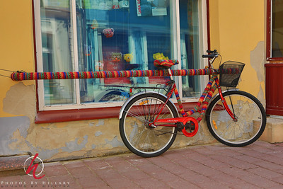 Daily Post 1163- 160/365   6/10/2014 - Yarn isn't just for sweaters any more. Loved the way this shop decorated their bike and the railing it was attached to. Quite fun, don't you agree? Made me want to take up knitting again...for about 3 minutes!   This was taken in Pärnu, Estonia. We are quite enchanted by this lovely town. We actually decided to stay here a total of 4 nights. It is full of the most amazing parks, cute shops and restaurants and situated on a gorgeous beach. The tourists are mostly from Finland and Germany here. Not much English spoken at all. People are quite surprised to hear we are from the US because it is so far away. Even more surprised we are here on our own and not on a tour. That made us feel pretty proud!   Thank you for your comments on yesterday's hot dog photo. I thought you might enjoy seeing those.