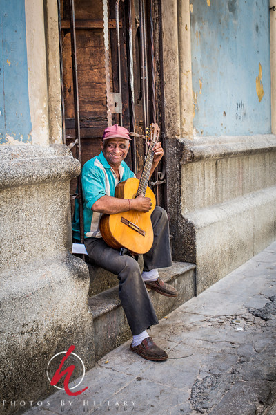 """<font size=""""3""""><font color=""""Yellow"""">Post 1043  8/365 1/8/2014  A smile to remember.   I photographed this fellow Tomas the first time on my first trip to Cuba November 2012. It was late in the afternoon and the light was getting low so that shot looked better converted to black and white. When I knew I was going to return to Havana again in June I made prints of many of the shots of people that I had taken on the first trip just in case I would see them again. What a fun surprise on this afternoon i June whent I saw this fellow just coming out of his doorway carrying that guitar just  like he had in November before. This time we had a chance to chat a little, I learned his name as Tomas and I was able to give him a print of the photo I had taken months before.    Here is the photo that I printed and was able to give him a copy of from the first trip.  <a href=""""http://www.photosbyhillary.com/Travel/Cuba/Havana-2012/28093006_rsWKgN#!i=2376947554&k=ZZ9ftmW&lb=1&s=A"""">Tomas</a>"""