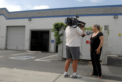 """VAN NUYS Ñ A television cameraman interviews a woman from a neighboring business.  Police say a porn actor killed one colleague and injured two others with a prop weapon during a late night showdown at the Van Nuys studio where they all worked. Police Detective Joel Price says the alleged attacker had been living at the adult entertainment business for several months but his colleagues told him he had to make other arrangements by Wednesday. Price says Steven Hill attacked a colleague in the back of the building after work Tuesday with a machete-like weapon. Price says two others who heard the man's screams ran to help him and were also attacked before Hill fled the scene. One of two people who tried to help died in surgery at a local hospital. The others are expected to survive. The victims' names have not been released. The assault at or near Hayvenhurst Avenue and Saticoy Street was reported about 10:20 p.m. Tuesday. Hill, described as a roughly 6-foot-tall man in his 30s, may have fled in a 1996 blue Toyota RAV with license 5YTC423, a Los Angeles police officer at the West Valley station said. The stabbings occurred at Ultima DVD Inc., which through its Ultima Entertainment division distributes pornography on the Internet and on DVD. According to the company's website www.ultimaentertainment.com, it specializes in """"adult fetish footage"""" that include scenes of """"... groin kicking ... female domination ... humiliation"""" and other sexual activities of a violent nature.  (Dean Musgrove/Staff Photographer)"""