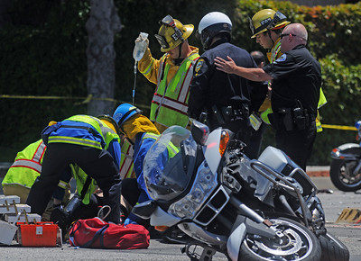 05-26-2011---Staff Photo by Sean Hiller--- Emergency crews work on an El Segundo police officer injured in a traffic accident which claimed the life of another motorcycle officer from the Hawthorne Police Department on Hawthorne Boulevard in Torrance Thursday afternoon. The crash occured during a funeral procession for Manhattan Beach officer Mark Vasquez.