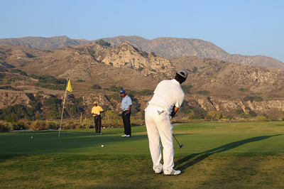 Fabian Romero putts his ball up onto the 16th green, while (r-l) Dwight Hicks and Kirk Adkins wait their turn. The mountains and wash surround this part of the back 9 holes at Angeles National Golf Course. The City Council today approved a long-awaited historic transfer of nearly 280 acres of open space from the Angeles National Golf Club to the Mountains Recreation and Conservation Authority (MRCA), elating the community that has worked for 15 years to ensure completion of the arrangement. Tujunga, CA. 11/16/2011(John McCoy/Staff Photographer)