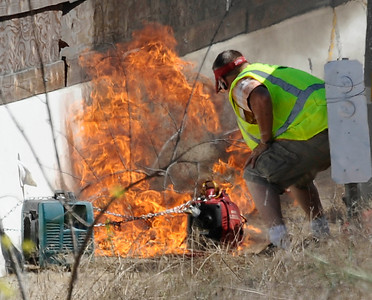 KABC TV crew member tries to put out fire from a generator as he was filling it up with fuel that almost set the brush on fire along the 405 freeway.  Work crews finish 17 hours ahead of schedule as the 405 freeway was reopen  around 11:30am this morning.   Los Angeles CA  July 17,2011. Photo by Gene Blevins/LA Daily News