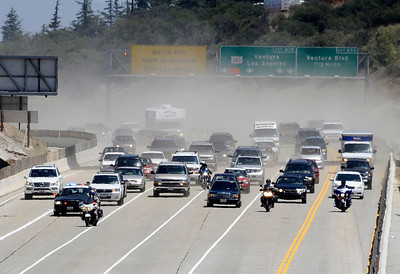 The first wave of cars to come south bound on the 405 in a dust cloud as work crews finish 17 hours ahead of schedule as the 405 freeway was reopen  around 11:30am this morning.   Los Angeles CA  July 17,2011. Photo by Gene Blevins/LA Daily News