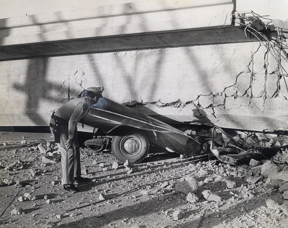 . The 1971 San Fernando earthquake (also known as Sylmar earthquake) struck the San Fernando Valley near Sylmar at 6:00:55 a.m. PST on February 9, 1971, with a magnitude of 6.6.  A Highway Patrol officer inspects the scene of the collapsed Foothill overcrossing on the northbound Golden State Freeway.  Two men, Art Mikkelsen of San Fernando and his passenger Milton Gonne of Van nuys were on their way to work. There are various names for this earthquake. Seismologists call it the San Fernando earthquake. USGS \'Sylmar Quake\' or \'Sylmar earthquake\' is the name initially given to the event by local media outlets, because the worst damage was to the Olive View Medical Center, located in Sylmar. Local veterans of \'the Sylmar Quake\' commonly refer to this seismic event as the \'February Ninth\' quake. (Daily News File Photos.)