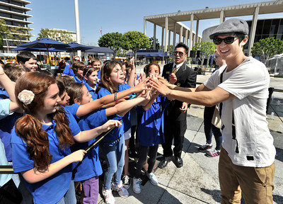 """Harry Shum Jr, from the hit TV Show """"Glee,"""" high fives children after he kicked up his heels with 3,000 students on the Music Center Plaza during The 41st Annual Blue Ribbon Children's Festival.  The Festival brings the experience of live performing arts to school children from 245 public, private and charter schools in Los Angeles County, free of charge.  More than 18,000 fifth grade students will attend performances on April 5, 6 and 7, 2011. Los Angeles, CA 4-5-2011. (John McCoy/staff photographer)"""