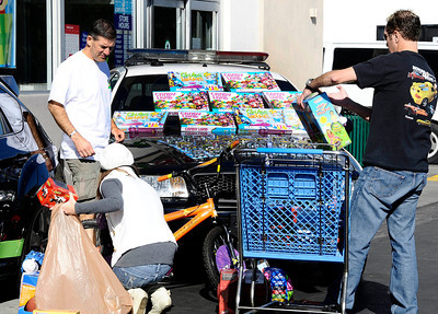 The owners of exotic and collectible cars along with the police officers   stack piles of new toys at the Toys R Us store to kick off the 7th Annual Motor 4 Toys Charitable Car Show. Woodland Hills CA. Nov 28,2010. photo by Gene Blevins/LA Daily News