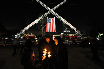 Community members Rick Seireeni, wife Elaine Kim Seireeni and daughter Echo Seireeni pay their respects  during a candlelight vigil at station 78 in Studio City for Los Angeles firefighter Glenn Allen, 61, who died of injuries suffered while battling a house fire in the Hollywood Hills. (Hans Gutknecht/Staff Photographer)