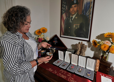 Maria Luisa Avneri opens  a hinged egg that she made to hold one of  her sons service medals. Maria is the mother of Jair De Jesus Garcia, a 28 year old Army private who was killed in Aug 2008 by a roadside bomb in Afghanistan. She has small memorial of him in her home that features his boots, medals, and an ostrich egg that she painted with his portrait on it. Northridge, CA. 9-6-2011. (John McCoy/Staff Photographer)