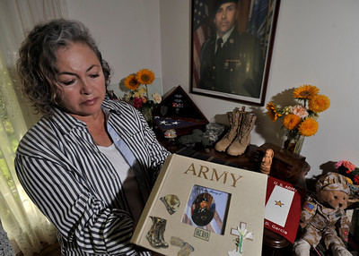 Maria Luisa Avneri holds a photo album of her son. Maria is the mother of Jair De Jesus Garcia, a 28 year old Army private who was killed in Aug 2008 by a roadside bomb in Afghanistan. She has small memorial of him in her home that features his boots, medals, and an ostrich egg that she painted with his portrait on it. Northridge, CA. 9-6-2011. (John McCoy/Staff Photographer)