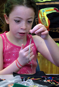Julia Winck, age 9, works on her embroidery.  Leora Raikin teaches African Folklore embroidery classes at Summer Art Academy, Art Camp in Agoura Hills, CA.   Students learn about beading and stitching as they learn about African wildlife and tribal arts.  (Dean Musgrove/Staff Photographer)