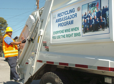 Recycling ambassador L.T. Gardner rides on the truck on Lemay Street to the next neighbor's home for search of more recycleables on Tuesday, July 3, 2007.  (Tina Burch/Staff Photographer)