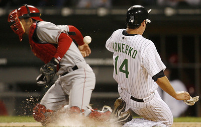 Chicago White Sox's Paul Konerko, right, scores as  Los Angeles Angels catcher Jeff Mathis misses the throw during the third inning of a baseball game Friday, Sept. 14, 2007, in Chicago. (AP Photo/Nam Y. Huh)