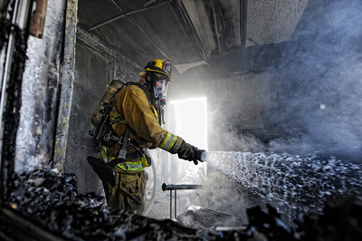 Los Angeles City Firefighter Gage Oetgen puts out some hot spots on a fire that gutted an Arrowhead Water distribution building 9400 block of Mason Ave, in Chatsworth Tuesday, April 3, 2012. It took 116 firefighters 29 minutes to knock down the blaze. (Hans Gutknecht/Staff Photographer)