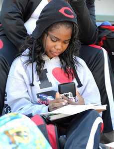 Ezinne Nwankwo does some homework after her Cleveland High School drill team finished its performance. The annual LAUSD Band and Drill Team Championship competition was held at East Los Angeles College. The competition featured an estimated 2,500 high school students representing 30 schools. The groups were evaluated on their visual ad musical performance. Monterey Park CA 12/10/2011(John McCoy/Staff Photographer)