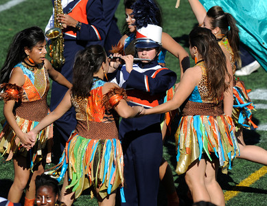 Chatsworth High School Marching Band Piccolo player Nicolas Nixholm is surrounded by Drill Team members wearing African inspired costumes. The annual LAUSD Band and Drill Team Championship competition was held at East Los Angeles College. The competition featured an estimated 2,500 high school students representing 30 schools. The groups were evaluated on their visual ad musical performance. Monterey Park CA 12/10/2011(John McCoy/Staff Photographer)
