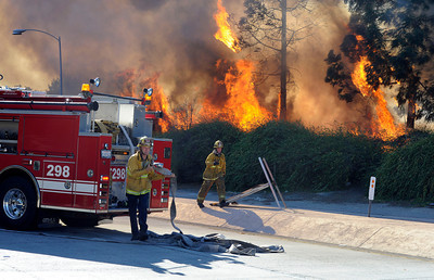 Los Angeles City firefighters battle a fire along the NB 405 freeway at the Devonshire exit in  Mission Hills. The fire started on the southbound side and soon jumped to the northbound side of the freeway causing both on and off ramps to be closed. It took 80 firefighters over a hour to knock down the flames.  (Hans Gutknecht/Staff Photographer)