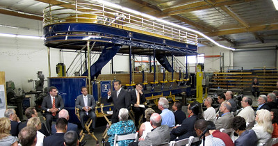Daymond Rice, Chair, VICA, Councilmember Mitch Englander, Mayor Antonio Villaraigosa and Deputy Mayor Matt Karatz during the roundtable.  Behind them is a self-powered hybrid heritage-style trolley that can carry 75 passengers.  The TIG/m plant in Chatsworth, provided the backdrop for the Mayor's roundtable with business leaders from across the City of Los Angeles, meeting to discuss their efforts to create jobs and lift the local economy out of recession.  TIG/m manufactures fully self-powered, sustainable-design streetcars, contributing to LA's role as a leading global clean technology hub and helping to grow the City's export economy by building projects around the world, including a 2,000 acre residential and recreational trolley system in Baja California and is currently working on a trolley system in a mixed-use development in San Antonio,TX.  They are also in the running to build a green trolley service in Doha, Qatar, and currently contracted for a system in Dubai, UAE. Their sustainable streetcars systems have been used to improve circulation and public transit use, revitalize urban cores, promote mixed-use development, and bring green transportation options to residential neighborhoods.  The Mayor's Office and the Minority Business Development Agency Business Center - Los Angeles (MBC-LA) have worked with TIG/m to help them identify financing and procure contracts around the country and internationally.  (Dean Musgrove/Staff Photographer)