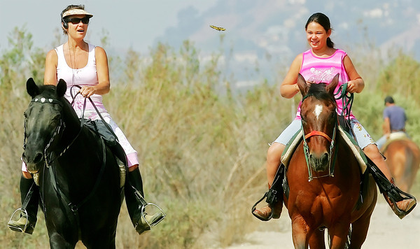 Sandra Louis and her daughter Natalie, 10, of Lake View Terrace, CA, marvel at a Western Tiger Swallowtail Butterfly as it crosses their path while they ride their horses Shadow and Pepper on a trail at the Hansen Dam Equestrian Center on Thursday, Aug. 23, 2007. (John Lazar/L.A. Daily News Staff Photographer)