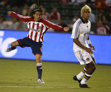 Chivas's Francisco Mendoza jumps in air along side of Galaxy Abel Xavier during the second half on Thursday, September 13, 2007 at Home Depot Center. (Edna T. Simpson)