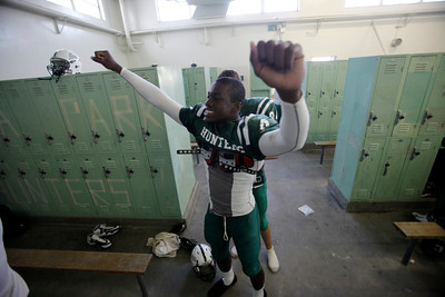 Canoga Park High School's Randy Uzoma gets some help putting on his jersey in the locker room before their game against Washington Prep at Canoga Park High School Wednesday, September 1, 2010. (Hans Gutknecht/Staff Photographer)