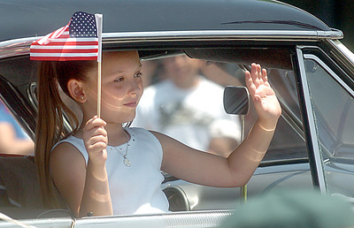 Faith Shaw, 7, of Chatsworth, waves from a1951 Ford Victoria during the 19th Annual Canoga Park Memorial Day Parade on Monday, May 28, 2007.  (Tina Burch/Staff Photographer)