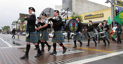 St. Patrick's Day was celebrated in Canoga Park, CA with a sidewalk parade, music and storytelling.  Light rain fell as the group moved from the Madrid Theater past Follow Your Heart along Sherman Way, Saturday March 17, 2012.  The Pasadena Scottish Pipe and Drums march across Sherman Way at Owensmouth.   (Dean Musgrove/Staff Photographer)