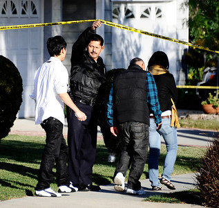 An LAPD officer lets family members cross a police line at the scene where an 89-year-old woman was struck and killed by an auto as it was backing out of the driveway at 19821 Buttonwillow Drive in Winnetka on Nov. 28, 2010. (Gene Blevins/Special to the Daily News)