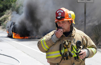 A fire department Captain communicates on his radio while the pickup burns behind him. A pickup truck experiencing mechanical problems pulled over to the side of the 2 freeway southbound, south of Colorado Blvd. at approximately 2 PM. Soon the vehicle became engulfed in flames that spread to the nearby grass and brush. The flame threatened nearby homes before being extinguished by Fire Department water dropping helicopters. Glendale, CA 5-31-2011. (John McCoy/Staff Photographer)