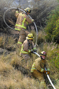 Firemen pull hose up a steep hillside next to the freeway. A pickup truck experiencing mechanical problems pulled over to the side of the 2 freeway southbound, south of Colorado Blvd. at approximately 2 PM. Soon the vehicle became engulfed in flames that spread to the nearby grass and brush. The flame threatened nearby homes before being extinguished by Fire Department water dropping helicopters. Glendale, CA 5-31-2011. (John McCoy/Staff Photographer)